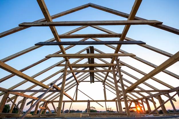 Nueva casa de madera en construcción. primer del marco del tejado del ático contra el cielo claro desde adentro. casa de ensueño ecológica de materiales naturales. concepto de construcción, construcción y renovación. Foto Premium