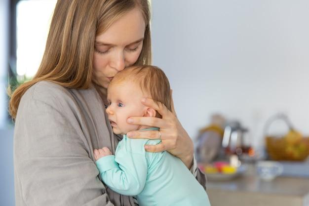 Nueva mamá abrazando y besando bebé Foto gratis