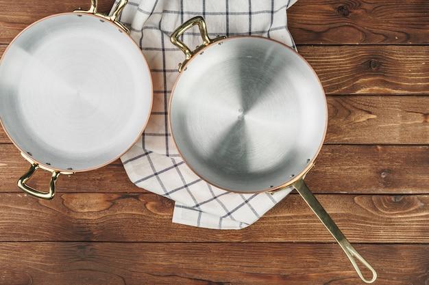 Nueva olla de cobre en la mesa de madera, vista desde arriba