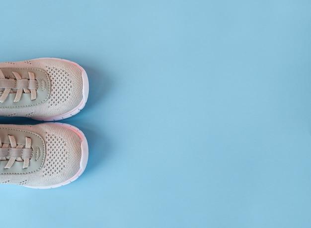 Nuevas zapatillas de deporte grises sobre fondo azul pastel Foto Premium