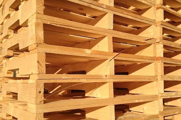 Nuevos palets de madera se apilan en el almacén de la empresa de entrega de carga. Foto Premium
