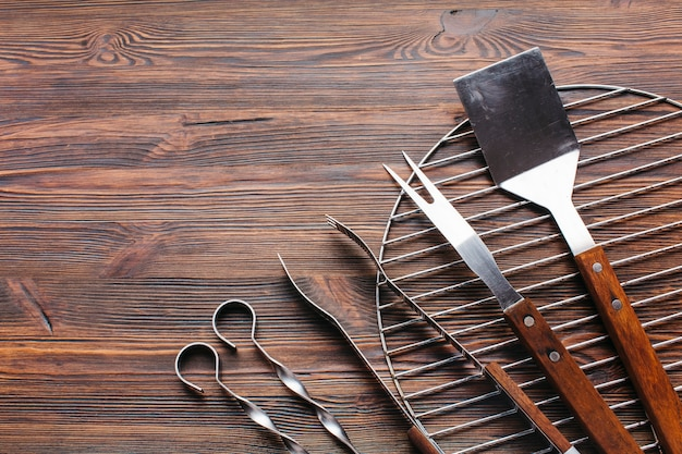 Nuevos utensilios metálicos de barbacoa sobre fondo de madera. Foto gratis
