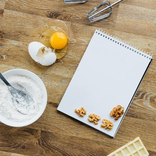 Nuez; bloc de notas espiral harina; chocolate y batidor sobre superficie de madera. Foto gratis