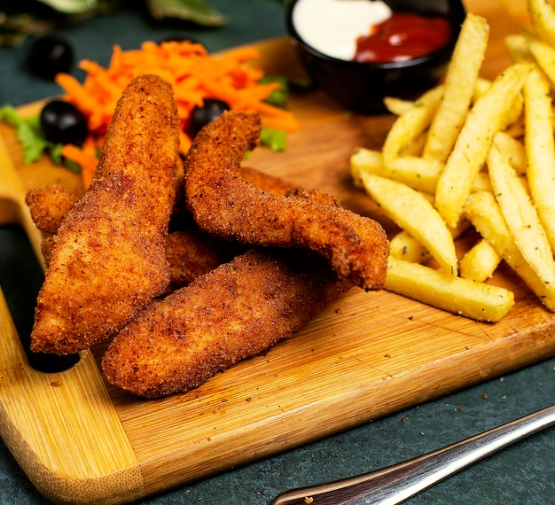 Nuggets de pollo al estilo kfc con papas fritas, mayonesa, ketchup y ensalada de verduras Foto gratis