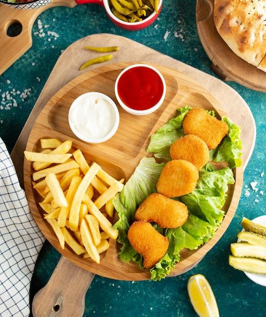Nuggets de pollo frito con papas fritas vista superior Foto gratis