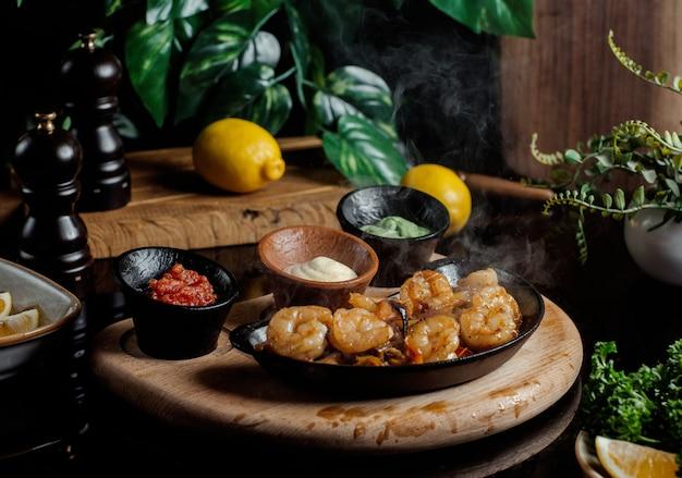 Nuggets de pollo servidos con pesto, crema y salsa de tomate dentro de cerámica negra Foto gratis