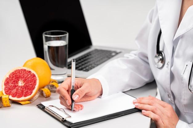 Nutricionista escribiendo en un portapapeles Foto gratis