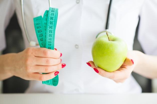 Nutricionista femenina y sosteniendo una manzana y una cinta métrica. Foto Premium