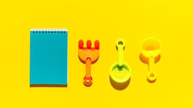 Objetos de la caja de arena de verano y bloc de notas en superficie brillante Foto gratis