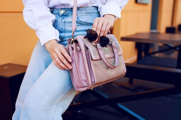 Objetos de moda. manos de mujer con bolso y gafas de sol. chica de moda sentado al aire libre. jeans con estilo. Foto gratis