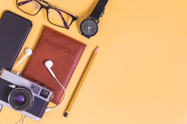 Objetos de viaje flatlay sobre fondo amarillo con espacio de copia Foto Premium