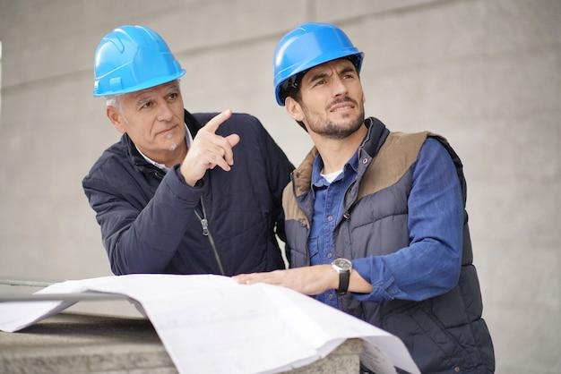 Obrero señalando y mostrando algo al empleado en la vista de un edificio moderno Foto Premium