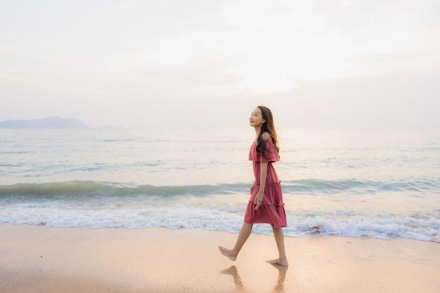 Ocio feliz de la sonrisa de la mujer asiática joven hermosa del retrato en el mar y el océano de la playa Foto gratis