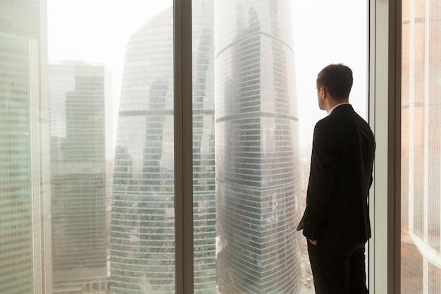 Oficial de la empresa mirando a través de la ventana en la oficina Foto gratis