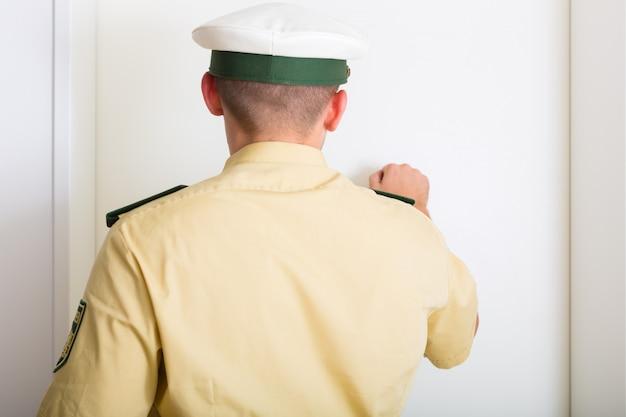 Oficial de policía golpeando la puerta de la casa Foto Premium