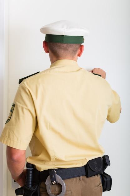 Oficial de policía tocando la puerta de casa Foto Premium