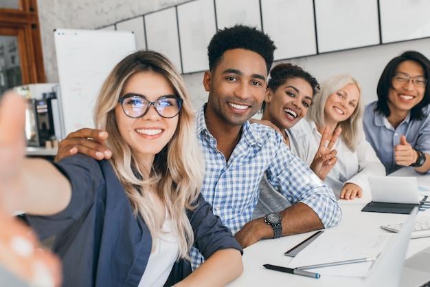 Oficinista negro en camisa a cuadros abrazando secretaria rubia mientras ella hace selfie. jóvenes directivos de empresa internacional divirtiéndose durante la reunión. Foto gratis