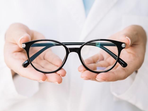 Oftalmólogo mostrando un par de anteojos Foto gratis
