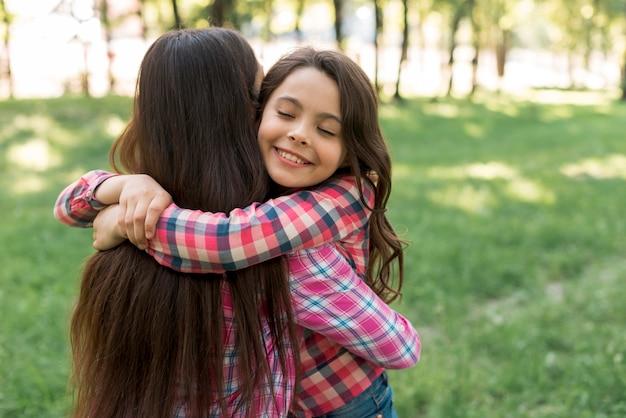 Ojos cerrados sonriendo linda niña abrazando a su madre en el parque Foto gratis
