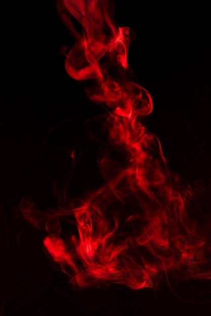 Olas de humo rojo brillante sobre fondo negro Foto gratis