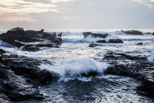 Las olas del océano se están rompiendo contra las rocas. salpicaduras de las olas del océano al atardecer. Foto gratis