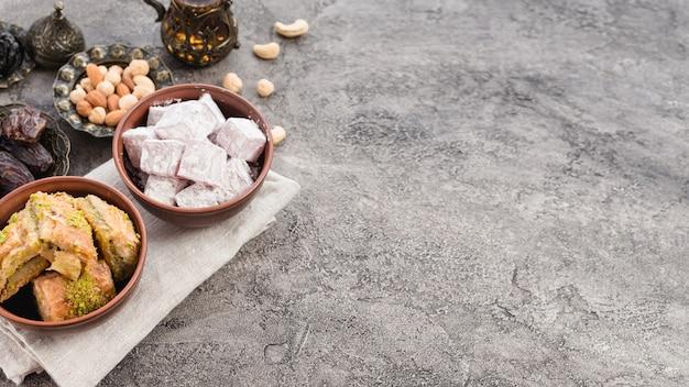 Olla de barro y cuenco metálico de lukum; baklava; fechas y frutos secos sobre fondo de hormigón. Foto gratis