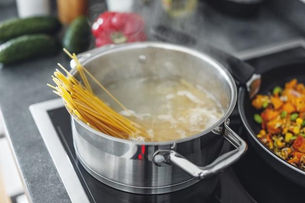 Olla hirviendo con cocinar pasta de espaguetis en la cocina. de cerca Foto gratis