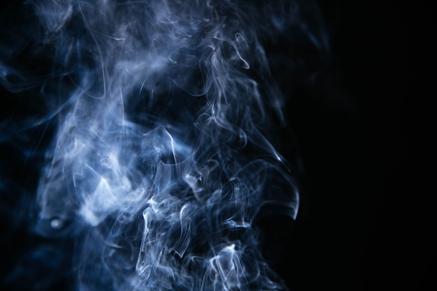 Ondas de humo azul sobre fondo negro Foto gratis