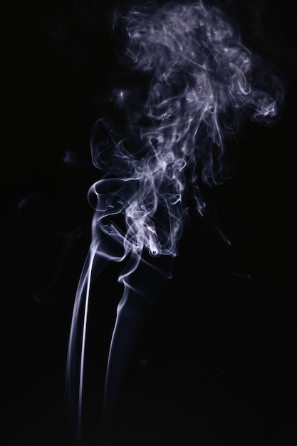 Ondas de humo gris sobre fondo negro Foto gratis