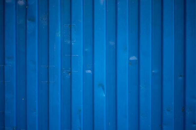 La ondulación azul de la pared del contenedor parece ondas en la textura del techo de zinc. Foto Premium