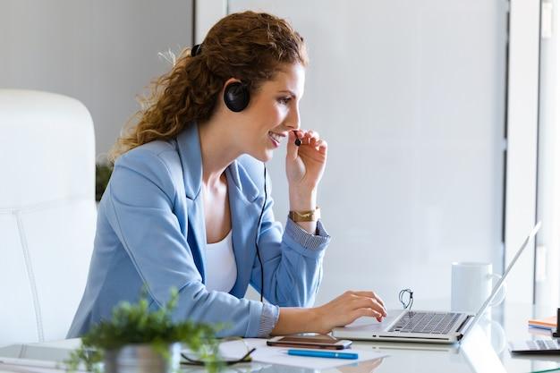 Operador de servicio al cliente hablando por teléfono en la oficina. Foto gratis
