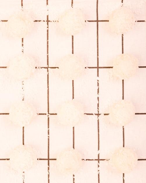 Opinión de alto ángulo del chocolate hecho en casa del coco dispuesto en una fila sobre el mantel a cuadros blanco Foto gratis