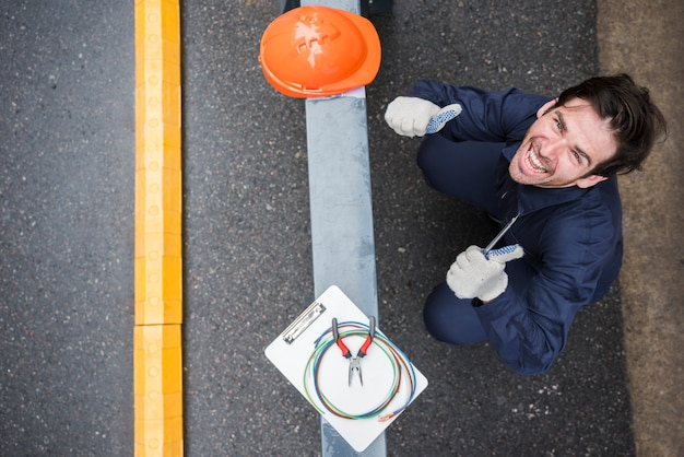 Opinión de alto ángulo el electricista de sexo masculino feliz que muestra el pulgar para arriba en el lugar de trabajo Foto gratis
