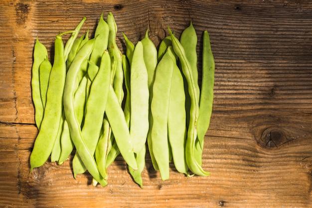 Opinión de alto ángulo de las habas de jacinto verdes frescas en el contexto de madera Foto gratis