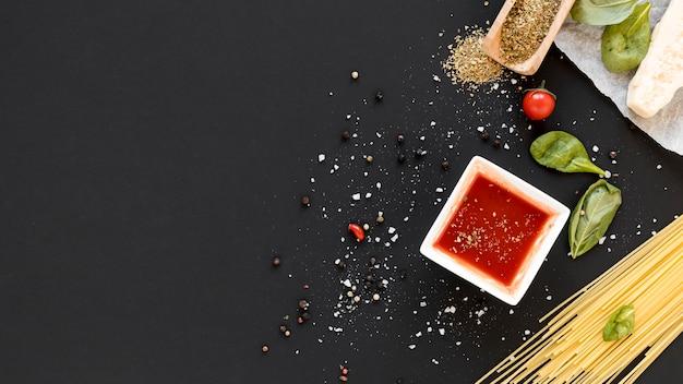 Opinión de alto ángulo de las pastas y del ingrediente crudos de los espaguetis en el contexto de la pizarra Foto Premium