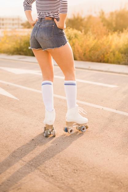 Opinión de ángulo bajo de la pierna de la mujer que lleva los pcteres de ruedas del vintage que se colocan en el camino Foto gratis
