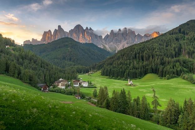 Opinión asombrosa de los paisajes de la colina verde y de la montaña con el cielo azul en la mañana de la salida del sol de las dolomías, italia. Foto Premium