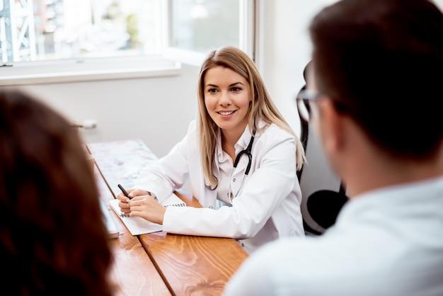 Opinión un doctor de sexo femenino atractivo joven que aconseja a un par joven de pacientes. Foto Premium