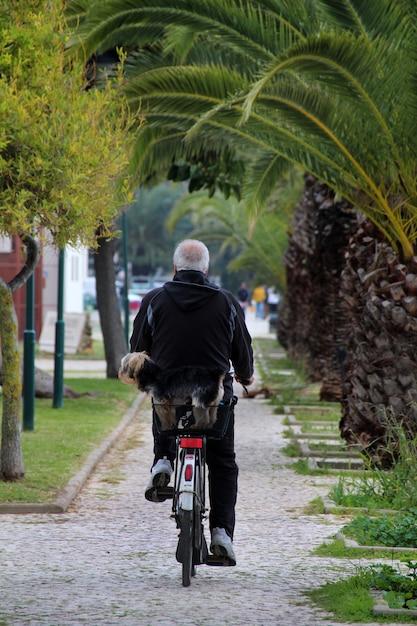 La opinión un hombre mayor que camina en una bicicleta con es perro casero. Foto Premium