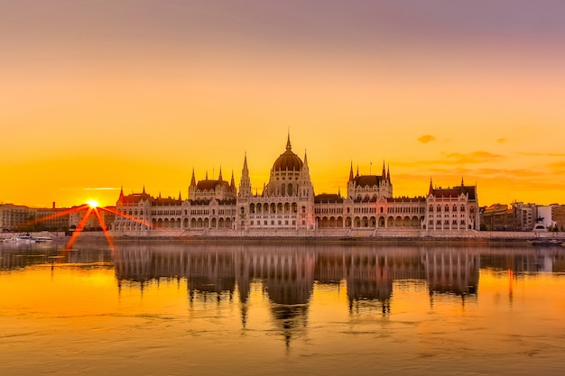 Opinión de la puesta del sol del edificio del parlamento de budapest con el río danubio en hungría. Foto Premium