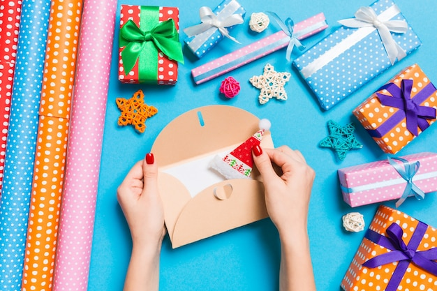 Opinión superior la mujer que sostiene un sobre, decoraciones del día de fiesta. concepto de tiempo de navidad Foto Premium
