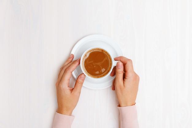 Opinión superior sobre las manos femeninas que sostienen una taza de café con leche en la tabla. Foto Premium
