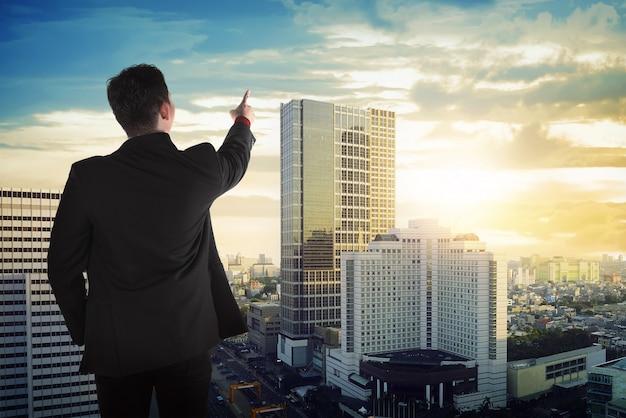 Opinión trasera el hombre de negocios asiático que mira el cielo Foto Premium