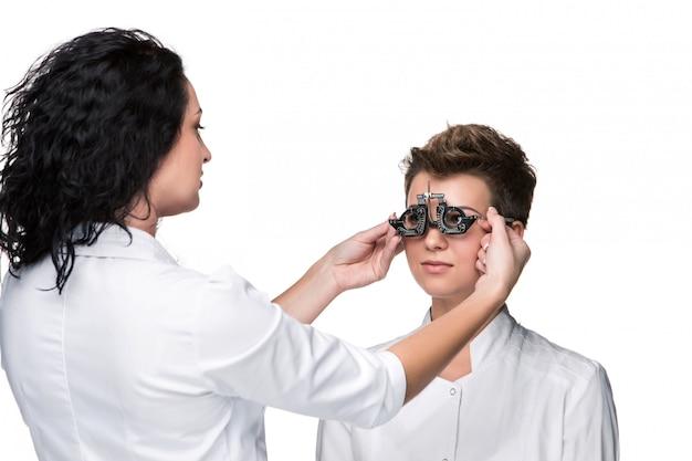 Optometrista sosteniendo un anteojos y dando al examen de mujer joven Foto gratis