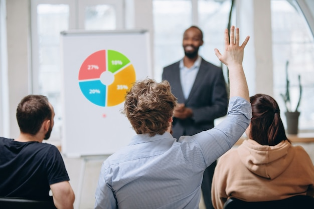 Orador masculino dando presentación en el salón del taller universitario. audiencia o sala de conferencias Foto gratis