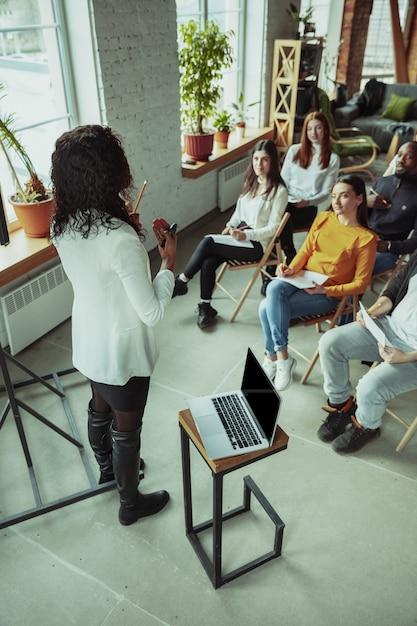 Oradora afroamericana dando presentación en el hall en el taller universitario Foto gratis