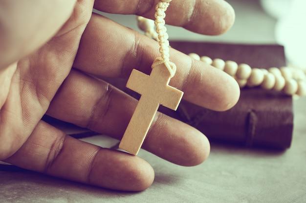 Orando las manos del pobre hombre con un rosario en la mesa de cemento oración, rosario Foto Premium