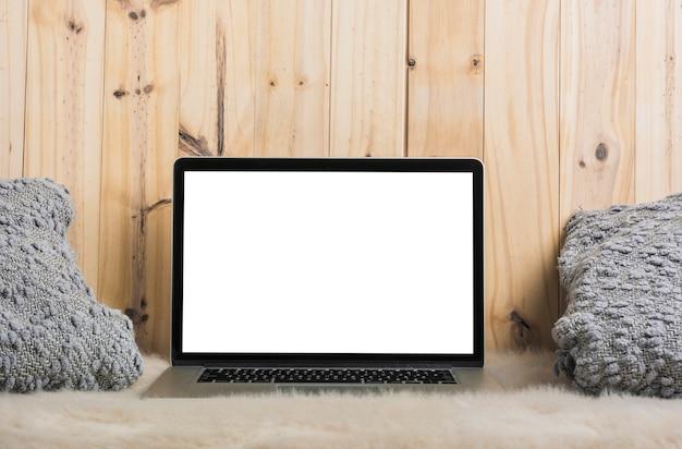 Ordenador portátil y almohada en piel suave contra el fondo de madera Foto gratis