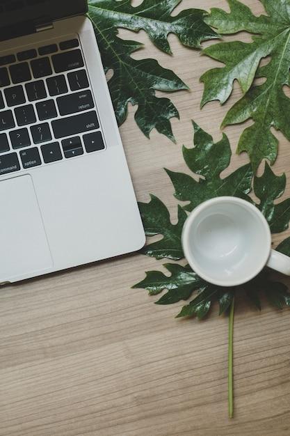 Ordenador portátil en una mesa de madera y una taza de café Foto Premium