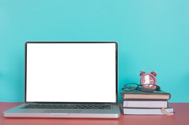 Ordenador portátil moderno con pantalla en blanco, libros, gafas y ...